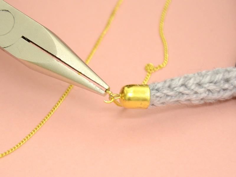 Passez la chaîne et l'anneau du pendentif dans l'anneau et fermez