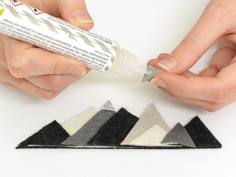 Découpez et collez des petits triangles de mousse pailletée (gris et gris clair) et collez-les au sommet de 3 des montagnes en feutrine.