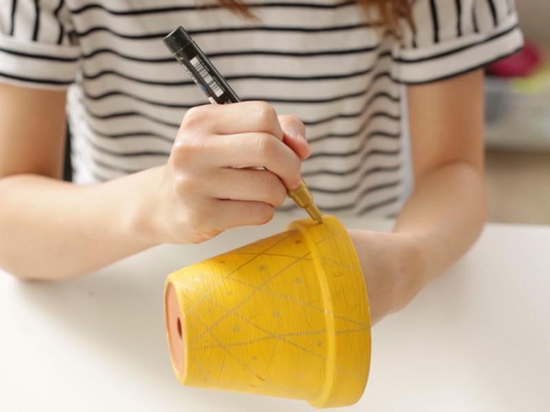Sur le pot ananas, tracer des quadrillages avec le Posca doré ainsi que des points entre les quadrillages.