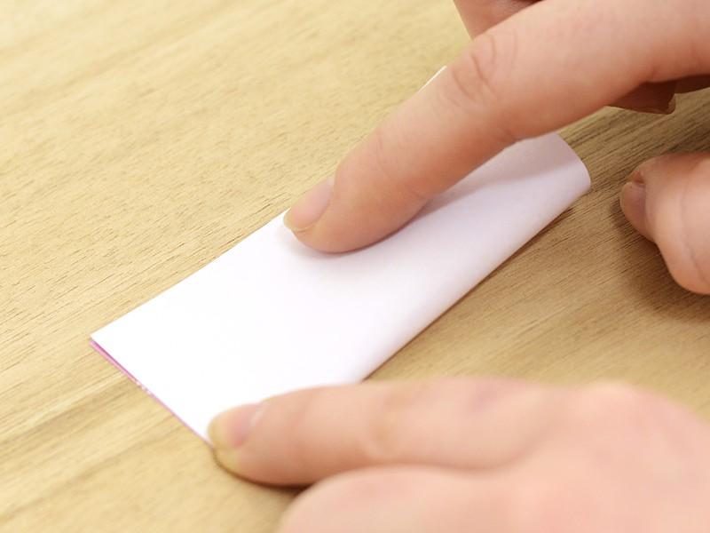 Plaçez votre papier devant vous, face illustrée sur le dessus et rabattez la partie inférieure sur la partie supérieure.