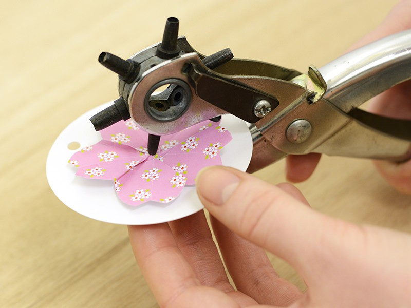 À l'aide des ciseaux ou du poinçon, faites un petit trou au centre de l'étiquette blanche et de la fleur.