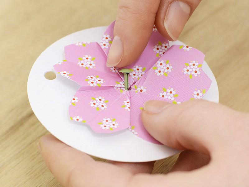Fixez la fleur sur l'étiquette avec une attache parisienne.