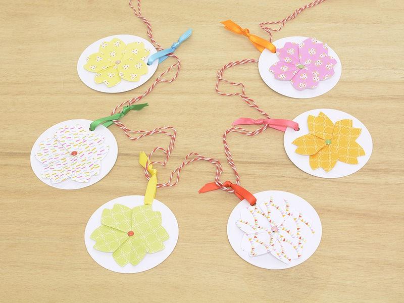 Confectionnez 5 autres fleurs et fixer les sur les étiquettes puis passer un fil dans les boucles des rubans colorés.