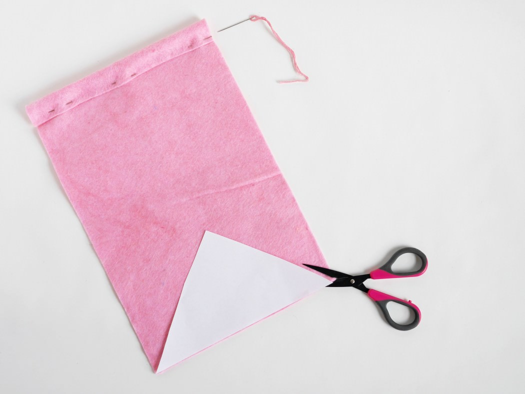 Découpez un triangle en bas de la feuille de feutrine pour former un fanion; en haut faites une pliure et cousez à 1,5cm du bord environ.
