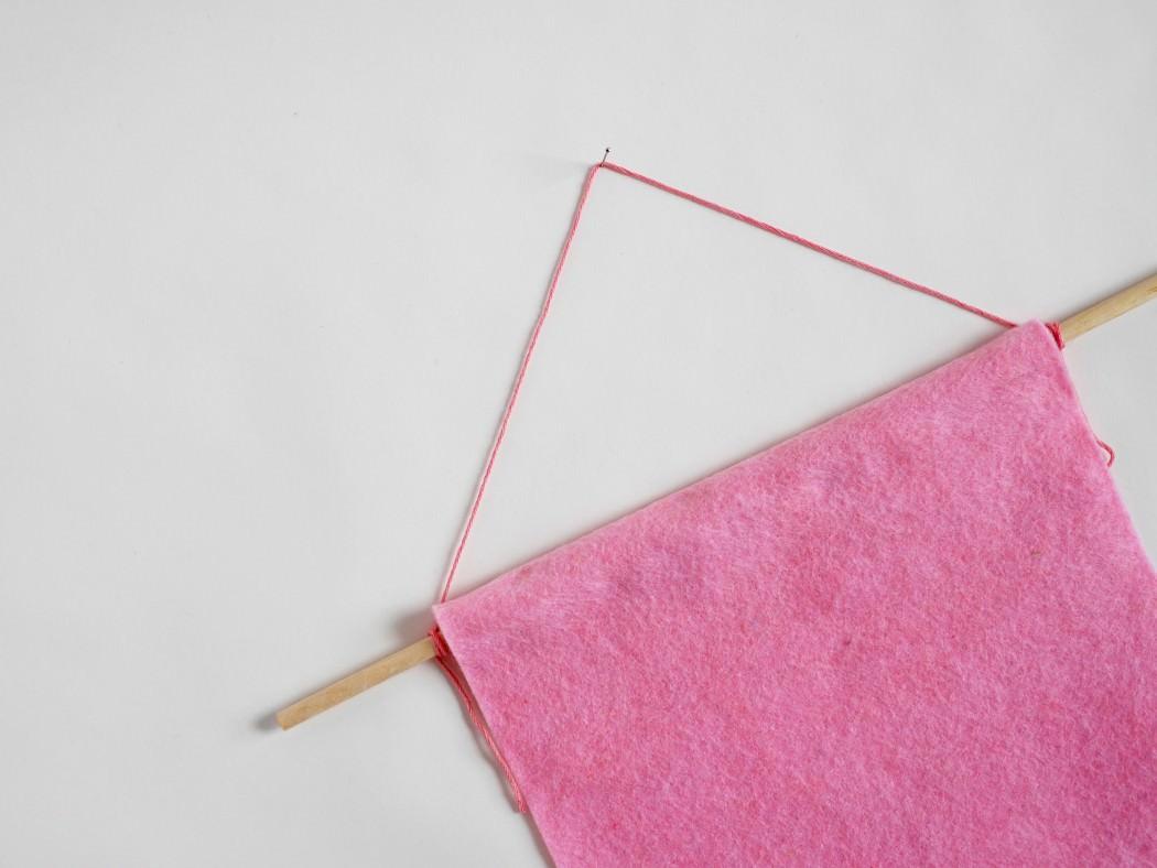 Passez votre baguette en haut du fanion et accrochez-y une ficelle assez longue pour pouvoir le suspendre, en faisant un noeud de chaque côté.