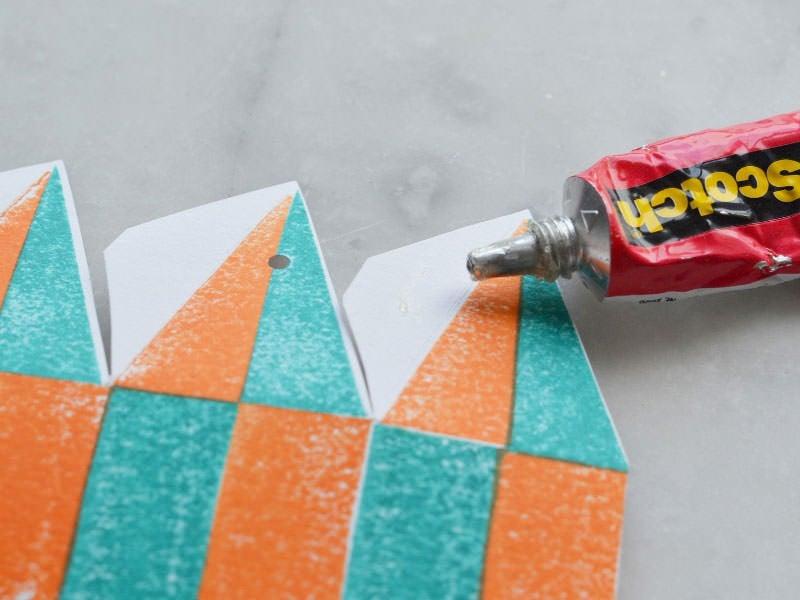 Perforez le haut aux endroits marqués sur le modèle. Commencez à coller les languettes de façon à monter peu à peu votre montgolfière.