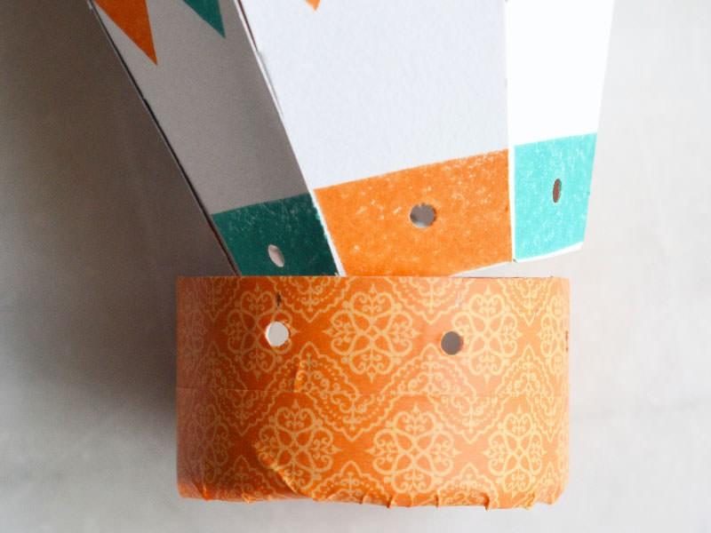 Collez du masking-tape sur le tronçon de rouleau en carton pour faire la nacelle. Perforez de sorte que les trous soient en face de ceux du ballon.