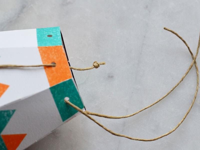 Coupez 6 morceau de ficelle d'environ 15 cm. Passez chaque morceau dans les trous et faites un double nœud à l'intérieur. Le fil doit ressortir et descendre vers le bas.