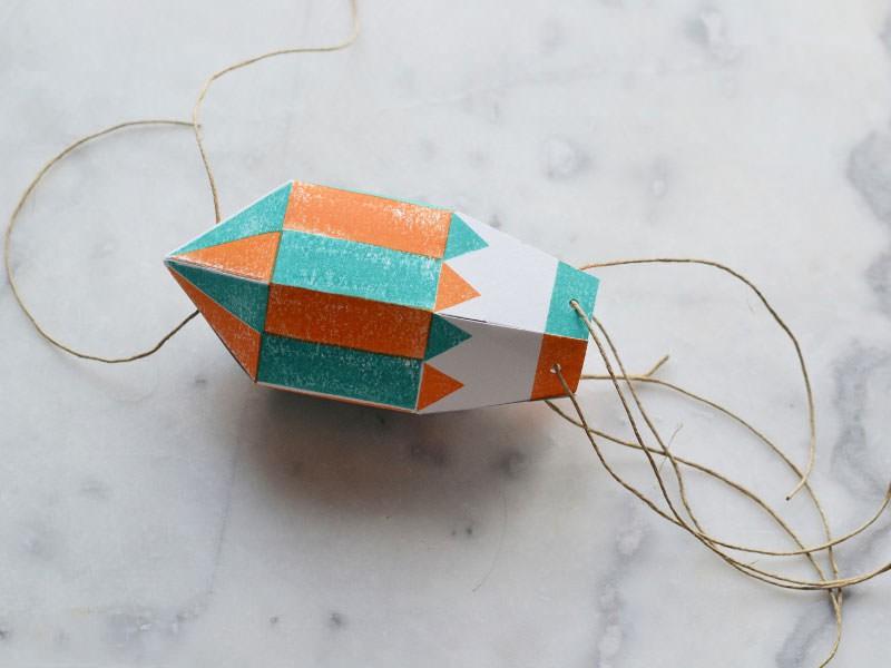 Faites de même 6 fois, et passez un fil de 20 cm dans les trous en haut, en terminant par un nœud, pour attacher votre montgolfière