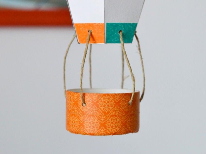 Attachez les fils à la nacelle, en faisant un nœud à l'intérieur. Vos fils doivent faire à peu près la même longueur. Vous pouvez attacher la montgolfière là-haut, et en refaire de différentes couleurs.