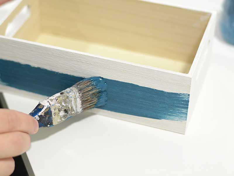 Quand la première couche de peinture est bien sèche appliquez la seconde (ici bleu pétrole). Mélangez la peinture avec un peu d'eau pour obtenir une légère transparence et ne pas avoir une couvrance totale