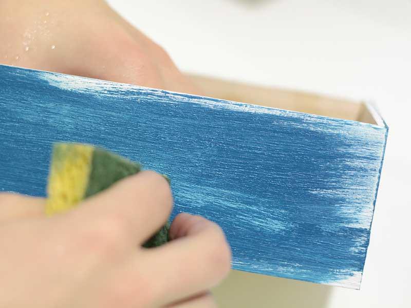 Utilisez les coins d'une éponge pour frottez la peinture et faire apparaître la sous-couche blanche à plusieurs endroits. Attention à ne pas étaler la peinture déhà présente sur l'éponge