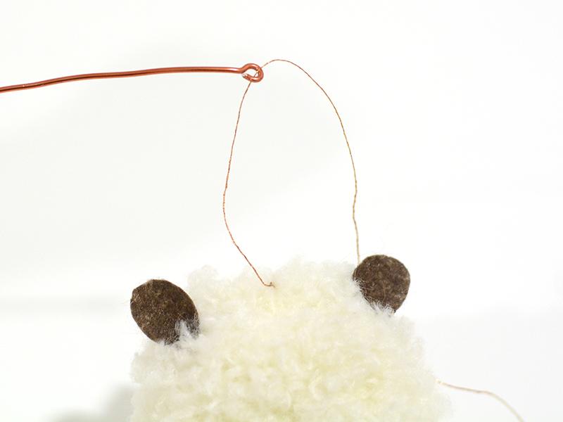 Faites des boucles au bout de tiges de fil d'alu et fixer-y vos pompons