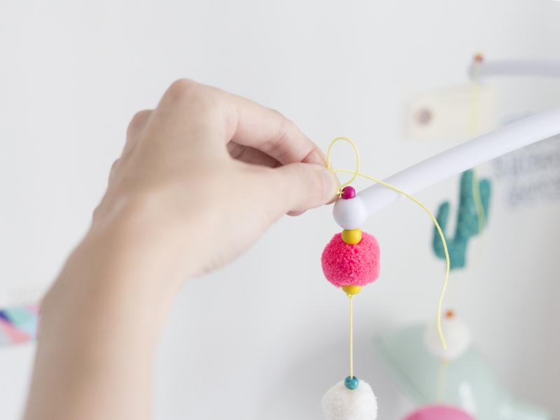 Passez votre fil dans une des extrémités du mobile, ré-enfilez une perle au dessus puis faites un noeud.