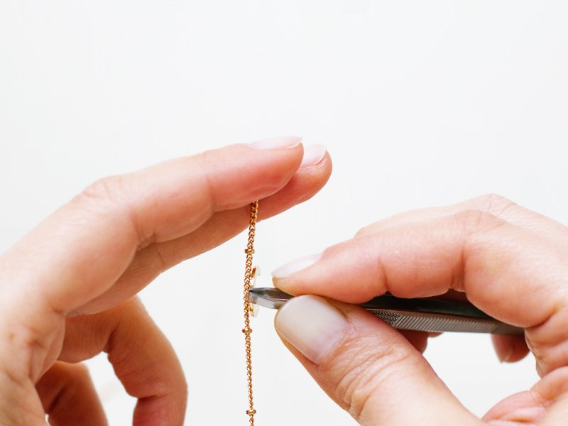 Coupez 60 cm de chaîne perlée. Insérez le pendentif lune sur l'anneau puis au milieu de la chaîne.