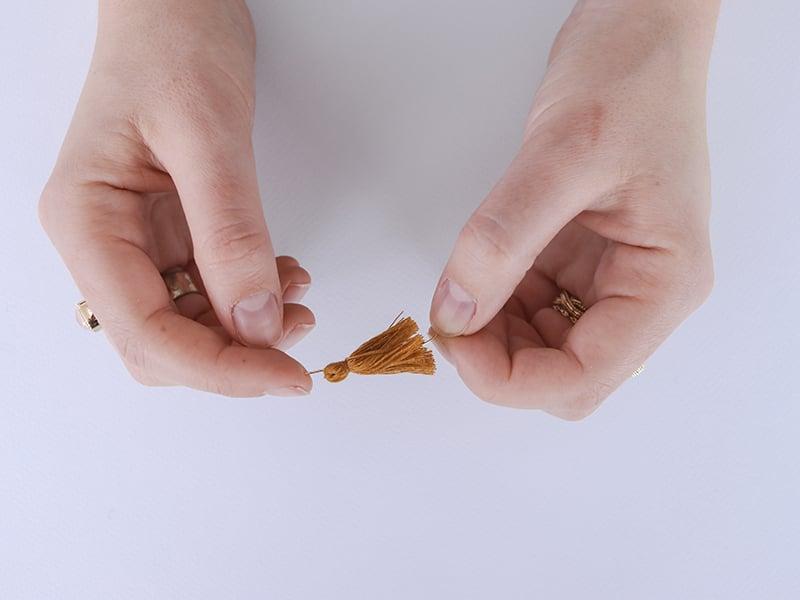 Plantez un clou dans chaque pompon par le bas, pour qu'il ressorte par la haut du pompon.