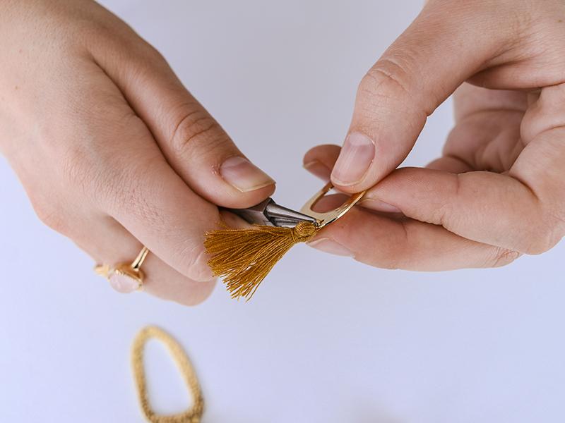 Fermez bien l'anneau pour que le pompon ne se détache pas.