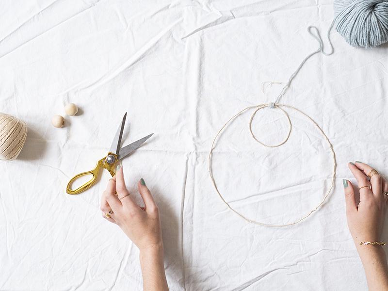 Une fois votre structure recouverte de fil, nouez le haut petit cercle avec le grand cercle grâce au fil Essentials Alpaca Blend Chunky. Faites un petit nœud et collez-le pour éviter que celui-ci se défasse après la coupure des fils.