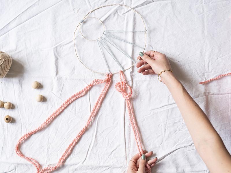 Nouer ces douze morceaux sur votre ouvrage comme ceci : faites passer votre fil de chaque côté (placez le milieu au niveau du cercle de votre suspension) puis glisser les deux bouts à l'intérieur de votre boucle. Placez et tirez vos fils pour fixer le nœud.