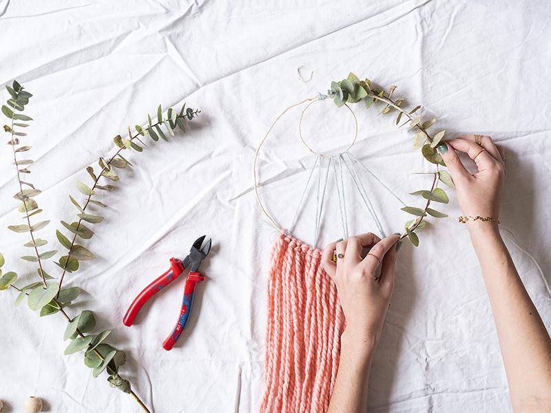 Une fois les franges accrochées, égalisez leurs longueurs puis choisissez vos branches d'eucalyptus, grandes de préférence. Enroulez-les autour de votre cercle : un fois au dessus, une fois au dessus. Servez-vous des feuilles pour camoufler la tige. Si votre branche principale n'est pas assez fournis en feuilles, ajoutez des petites branches pour lui donner du volume.