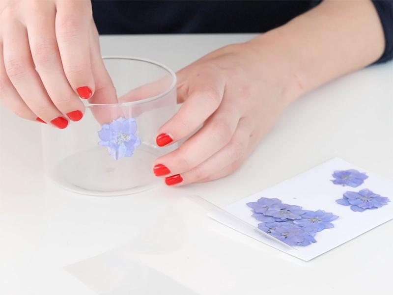 Puis collez une première fleur face contre le verre. N'hésitez pas à bien coller la fleur pour que la cire ne se glisse pas entre elle et le verre.