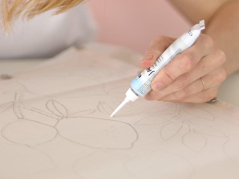 Repassez ensuite les traits de crayon à la gutta. La gutta va permettre de créer un «barrage à la peinture» et de délimiter vos motifs.