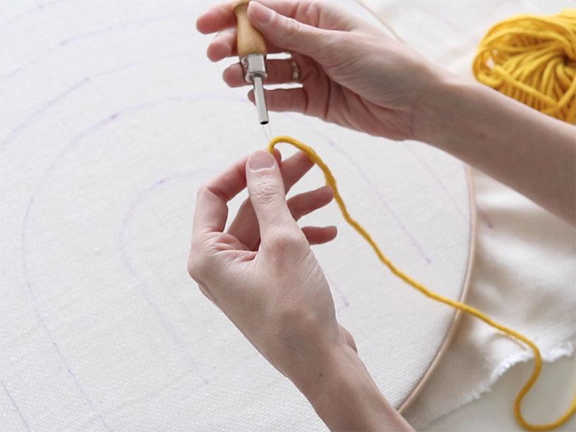 Insérez la laine dans la punch needle grâce à un enfileur.