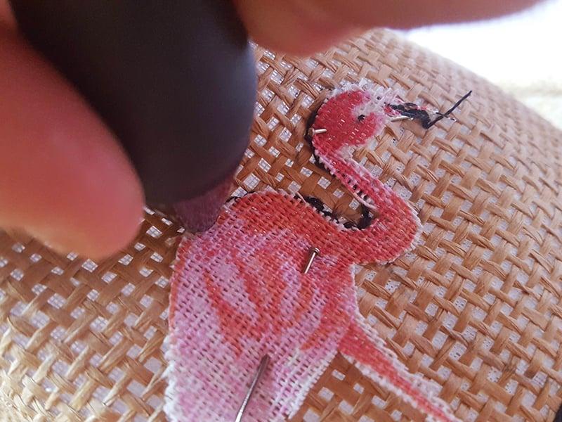 Commencez par découper votre motif flamant rose à la taille de votre choix puis fixez le sur le chapeau à l'aide de petites aiguilles à bout rond.