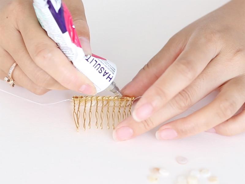 Déposez de la colle à l'arrière puis rabattez les fils pour fixer les perles