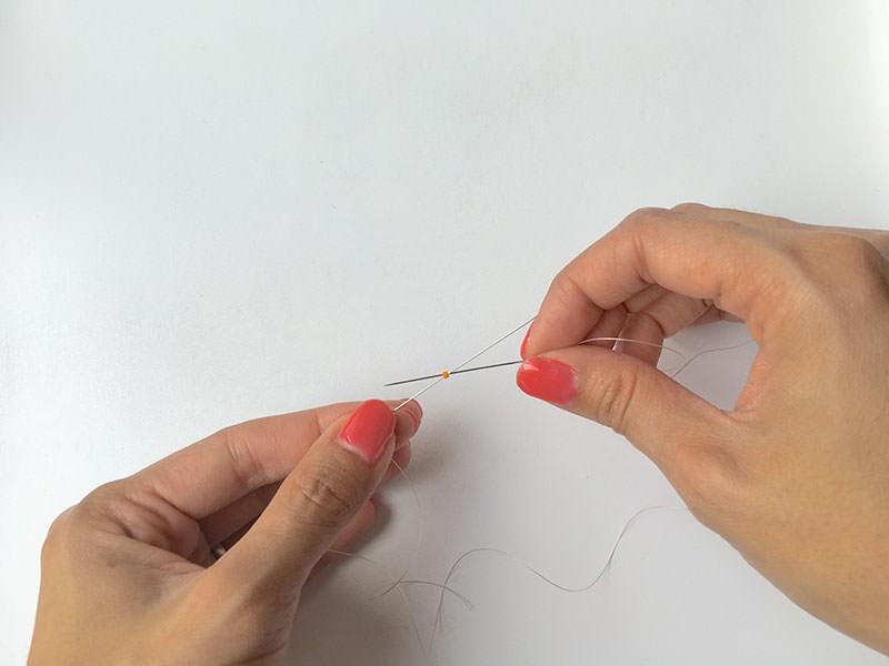 Enfilez une aiguille à chaque extrémité du fil. Enfilez la première perle rose et laissez la au milieu du fil. Enfilez directement la 2ème perle orange et croisez l'autre aiguille dans cette dernière.
