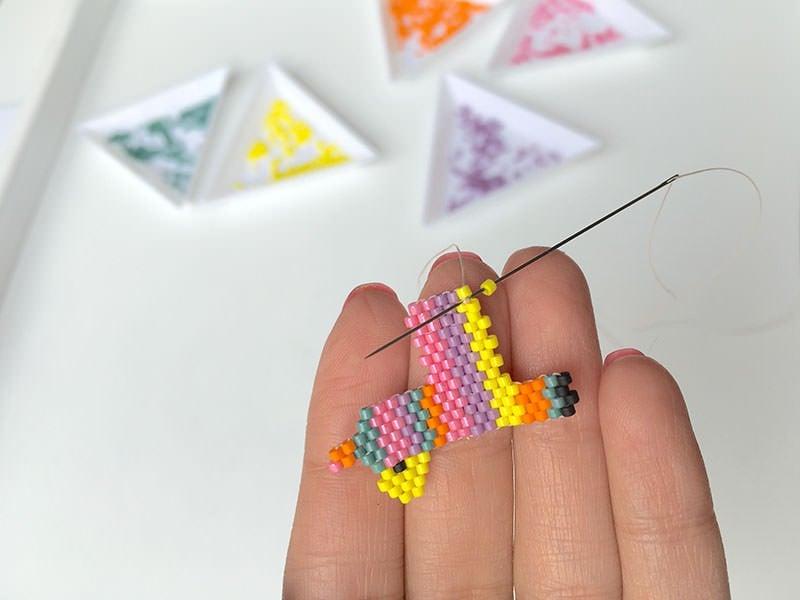 Pour réaliser les pattes arrières, vous aurez une augmentation de plusieurs perles à faire. Pour cela, procédez d'abord comme pour l'augmentation en fin de rang : Enfilez la perle, passez sous le fil et repassez votre aiguille dans la perle enfilée.