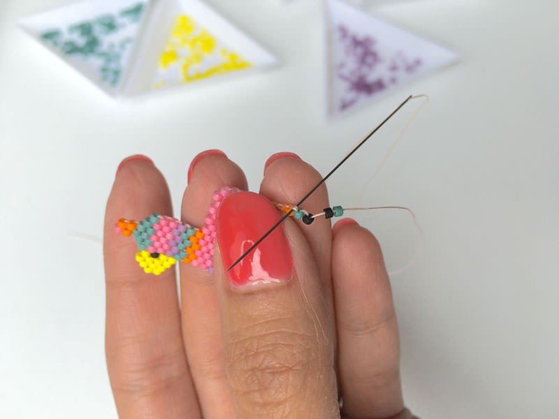 Enfilez directement les deux premières perles du rang, et passez votre aiguille sous le deuxième fil qui se présente à vous. Repassez votre aiguille dans la deuxième perle enfilée.