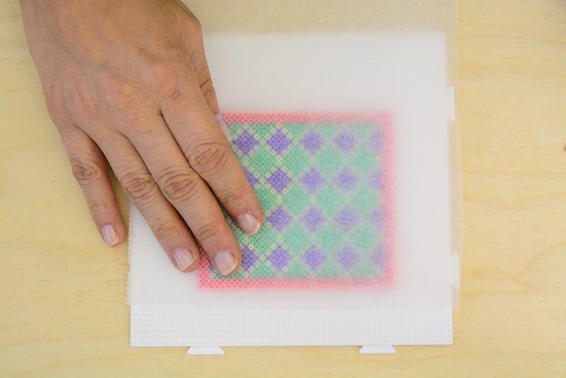 Placez délicatement un morceau de papier sulfurisé (papier de cuisson) sur votre création en perles Hama.