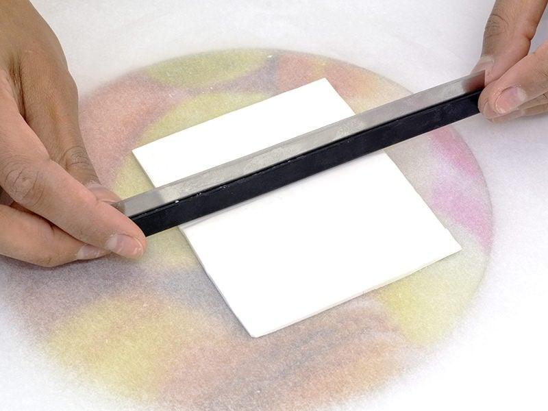 Avec le revers de la lame, marquez les emplacements où vous viendrez poser les échantillons de pâte bleue.