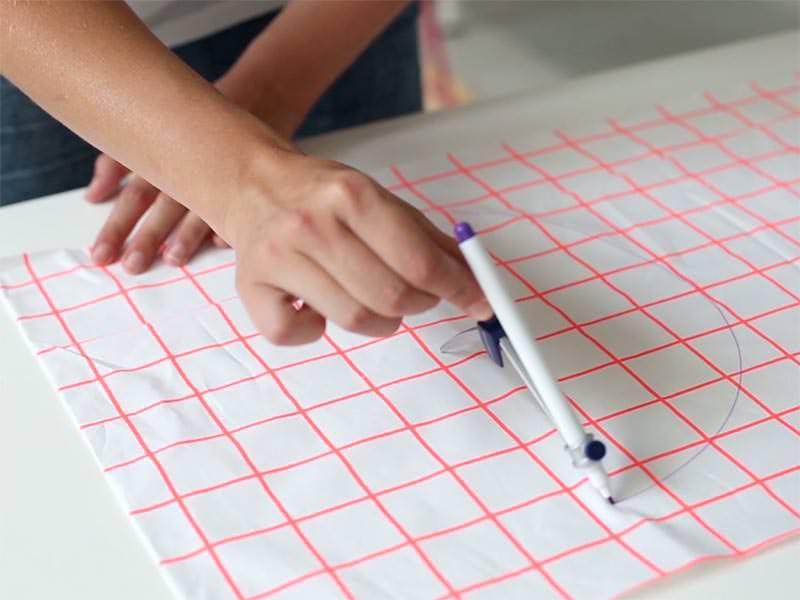 A l'aide du compas et du stylo effaçable à l'air, faites un rond avec votre tissu extérieur, plus grand que le diamètre de votre panier et découpez-le.