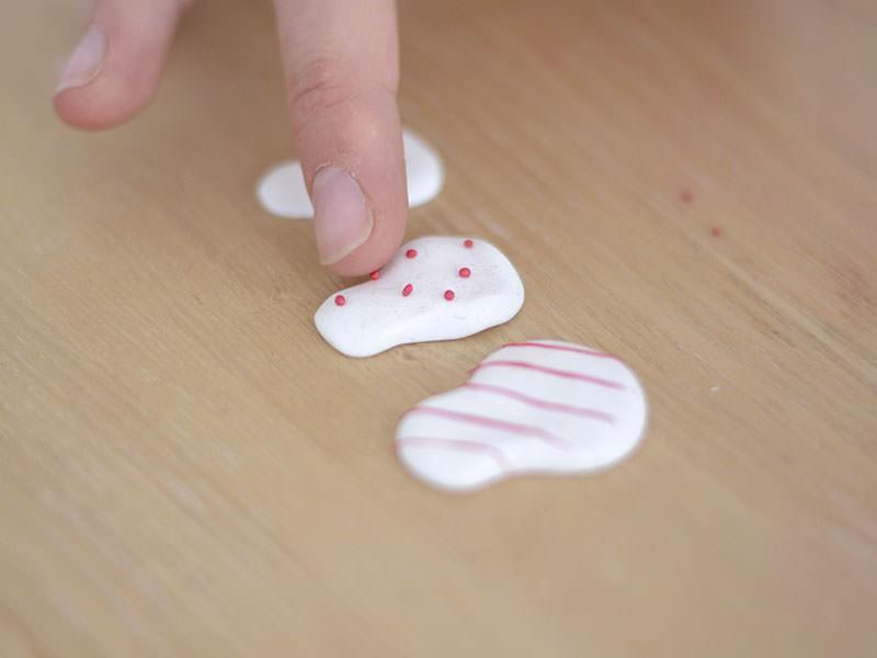 Sur la 2ème poupée, déposez des toutes petites boules de pâte rouge.