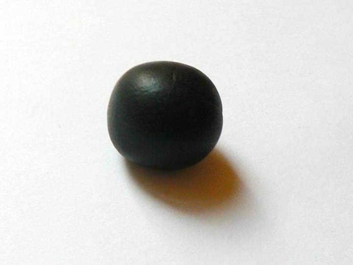 Prenez de la pâte Fimo noire de manière à pouvoir faire une boule environ de la taille d'une cerise.
