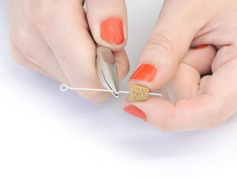 A l'aide d'une pince plate, enfoncez un clou à oeil au centre du bouchon de la fiole.