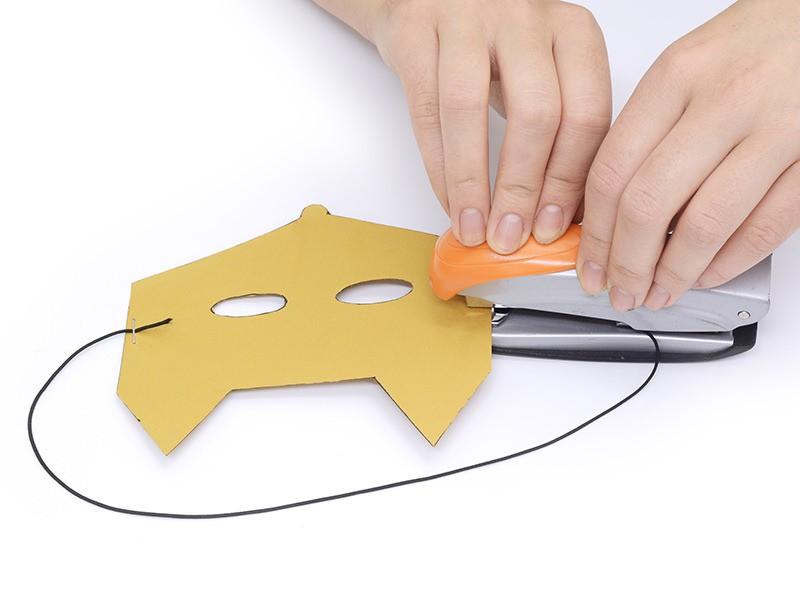 Découpez environ 40 cm de cordon élastique (à adapter selon votre tour de tête) et agrafez-le sur les côtés du masque en papier.