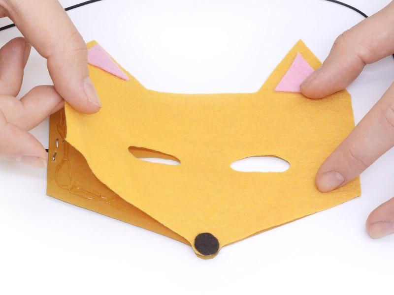 et venez déposer délicatement le masque en feutrine par dessus le masque en papier. Appuyez bien pour faire adhérer la feutrine à la colle.