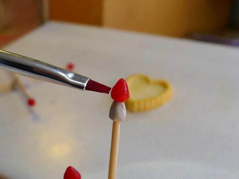 Colorez les fraises après les avoir cuites avec de l'encre ou de la peinture acrylique rouge. Mettez un peu de pâte non-cuite sur le bout d'un pic à cocktail et mettez la fraise dessus pour pouvoir la colorer plus facilement.