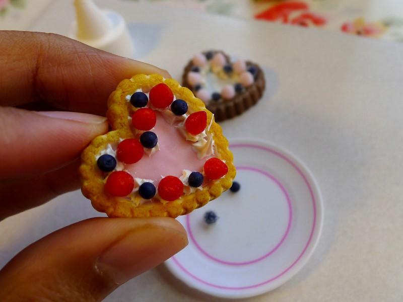Placez doucement un fruit sur chaque pointe de chantilly en alternant les fraises et les myrtilles. Attendez que le silicone sèche avant d'y toucher et de servir le gâteau à vos poupées.