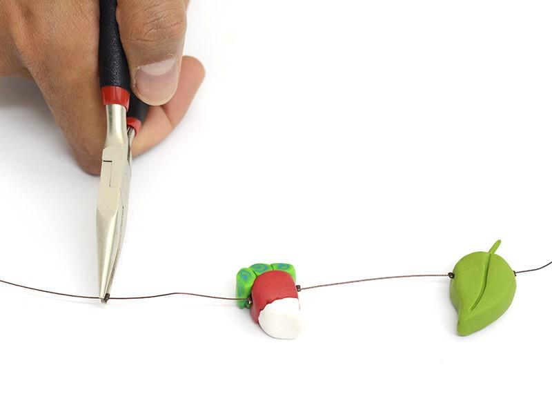 Enfilez les figurines sur le fil, en plaçant des perles à écraser sur le fil avec une pince plate empêcher les figurines de bouger.