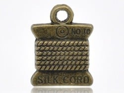 1 bronze-coloured spool charm