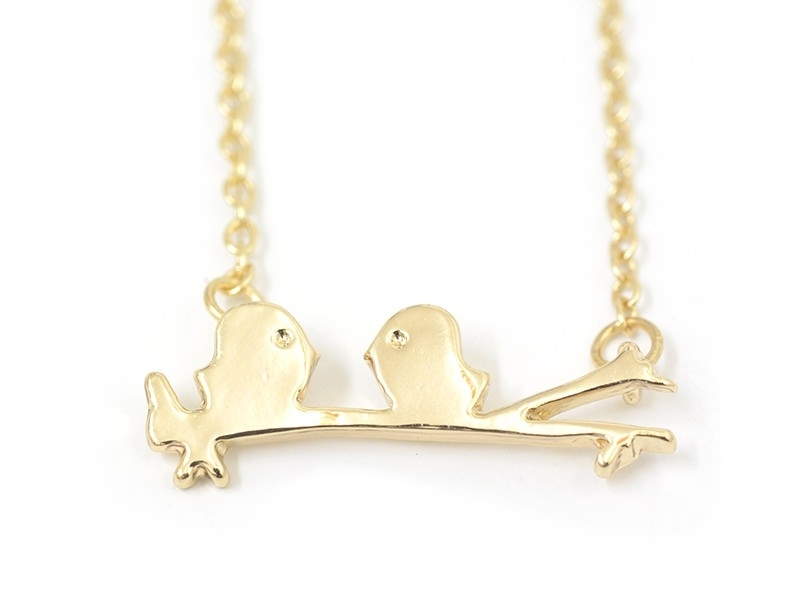 Delicate bird sitting on a tree necklace - gold-coloured