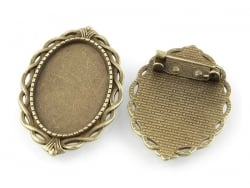 1 ovaler, bronzefarbener Broschenrohling mit Cabochonfassung und verziertem Rand - 42 mm