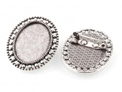 1 oval, silver-coloured brooch blank with a cabochon setting and a fancy edge - 33 mm
